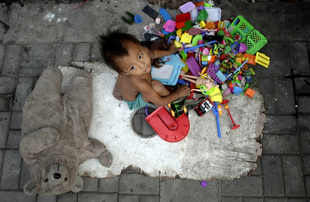 afp. hét képei - 2016.01.13. Manila, Fülöp-szigetek, hajléktalan kisfiú játszik, - A homeless boy plays with different toys collected by his parents that picks used plastic soda bottles to sell at junk shops in Manila on January 13, 2016.