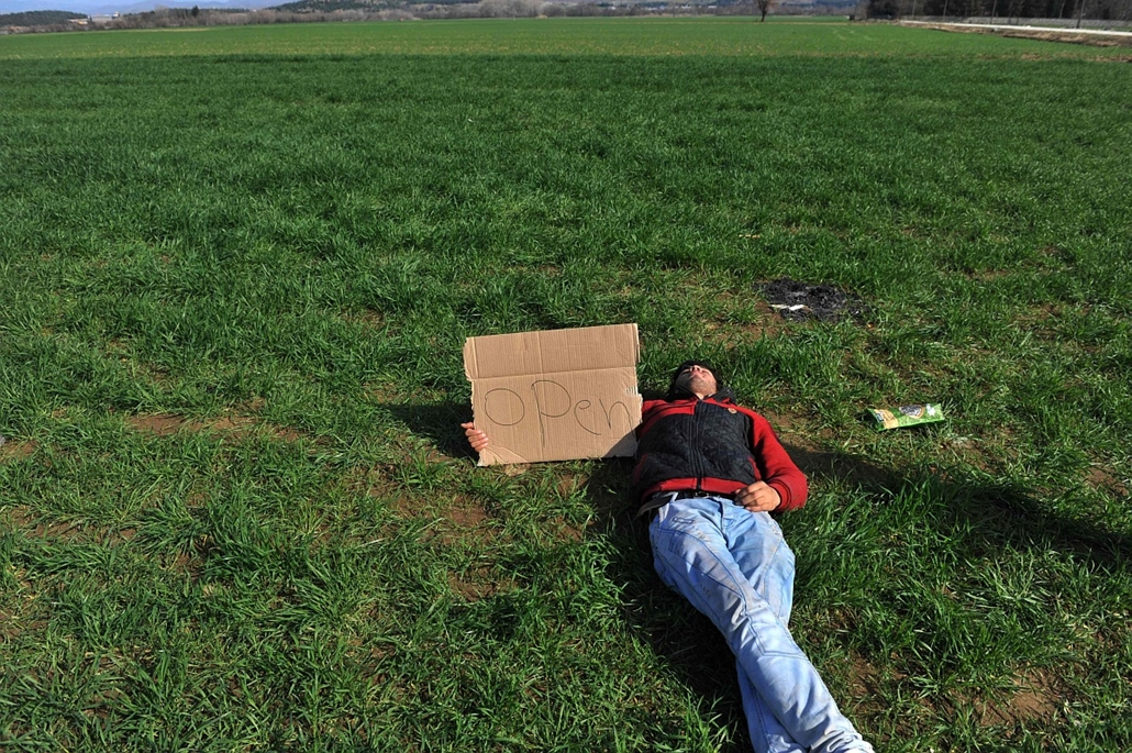 afp. hét képei - menekült, migráns, bevándorlás, 2015.02.22. afganisztáni menekült, Görög-macedón határon, A man lies on the ground with a placard while refugees from Afghanistan protest against the closure of the Greek-Macedonian border near the village