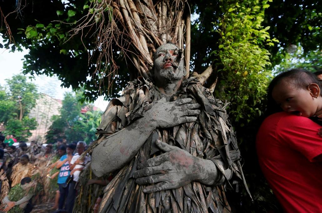 hét képei - !!! AP jú.6-ig !!! - Száraz banánleveleket visel egy sárral bekent Fülöp-szigeteki katolikus hívõ a Keresztelõ Szent Jánost ünneplõ sárfesztiválon a Nueva Ecija tartománybeli Bibiclat faluban 2016. június 24-én.