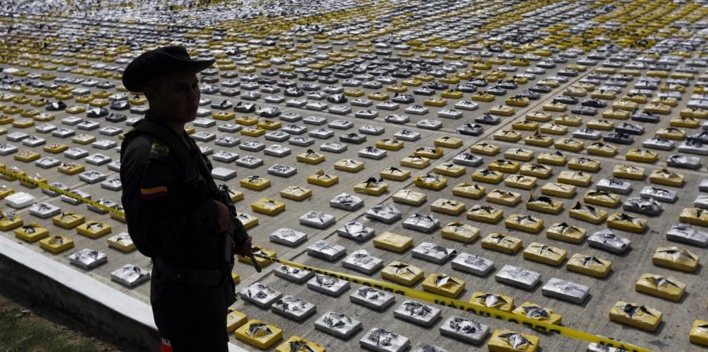 AP_! - márc.10-ig_! - 15.02.24. - Necocli, Kolumbia: Elkobzott, kokaint tartalmazó csomagok előtt áll a kolumbiai kábítószerellenes rendőrség egyik tagja Necocliban, 7képei
