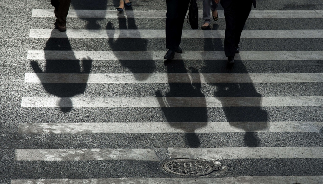 afp. hét képei - Shanghai, Kína, 2014.10.28. árnyékok, Commuters cast their shadow while walking across a street in Pudong's Lujiazui Financial District in Shanghai on October 28, 2014. The Chinese economy expanded 7.3 percent in the third quarter, lower
