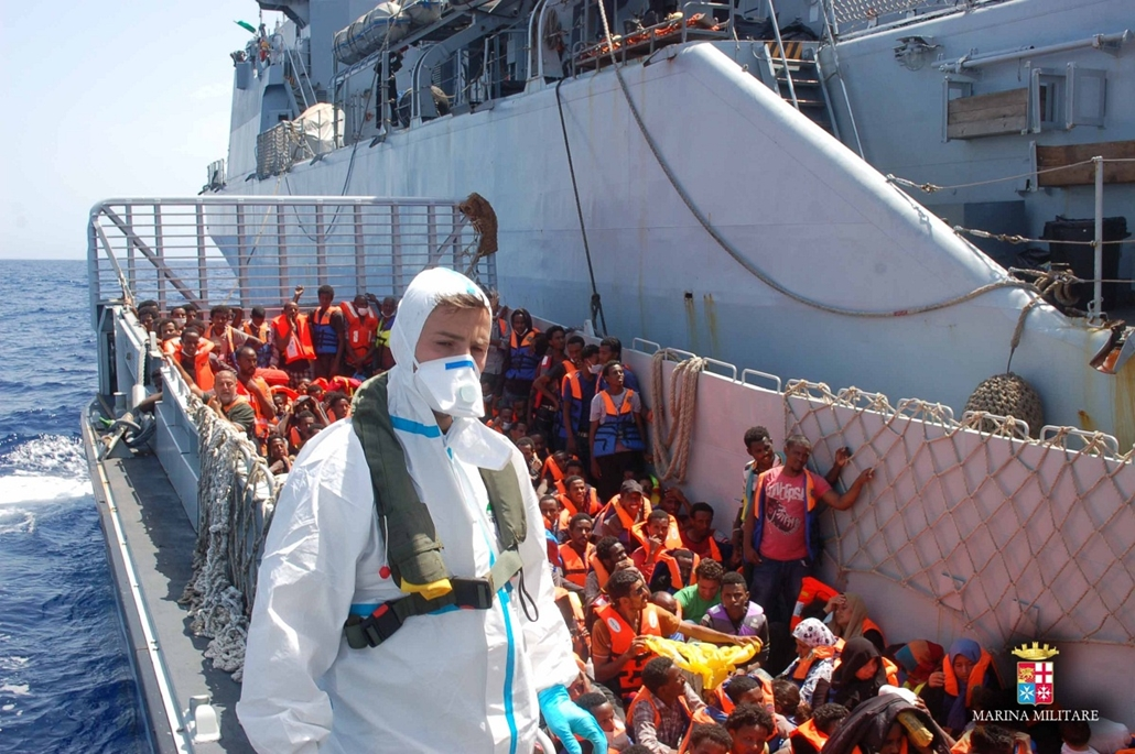 This handout picture released by the Italian Navy on August 23, 2014 shows rescuers of the Italian Navy and refugees on a boat near the Italian port of Pozzallo, south of Sicily.  The European Union's Home Affairs Commissioner Cecilia Malmstroem said on A