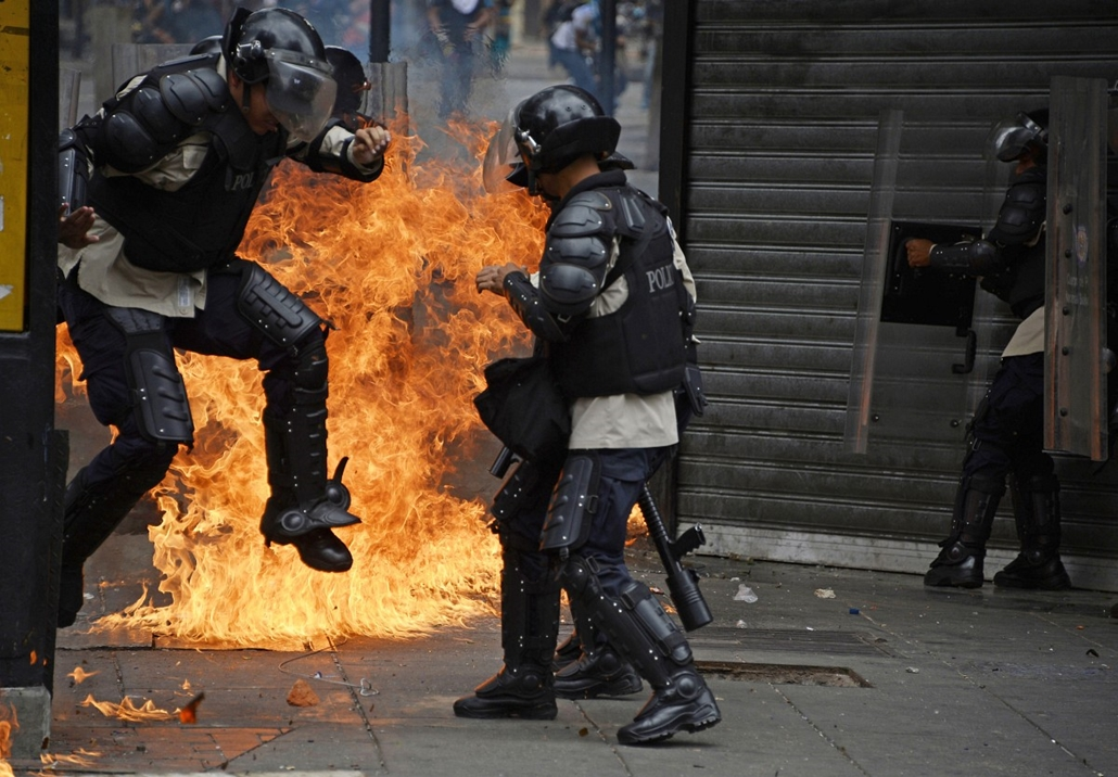 afp. Venezuela, tüntetés, rendőr, tűz 2014.04.17. Caracas - A member of the National Police runs away from fire after anti-government protesters threw a Molotov cocktail at them during clashes in Caracas on April 17, 2014. Anti-government protests have ra