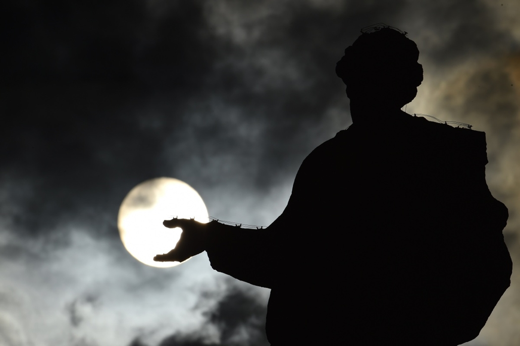 afp. hét képei - Vatikán, 2014.10.29. A picture shows the silhouette of a statue at St Peter's square as the sun rises through clouds before a general audience of pope Francis on October 29, 2014 at the Vatican.