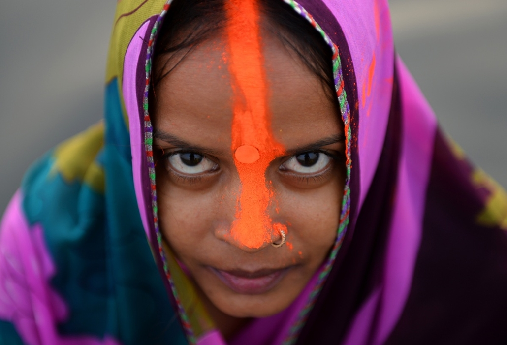 afp. hét képei - Újdelhi, India, 2014.10.28. hindu hívő, An Indian Hindu devotee poses for a photograph as she offers prayers a day ahead of the Chhat festival on the Yamuna river in New Delhi on October 28, 2014. The Chhat festival is dedicated to Lord S