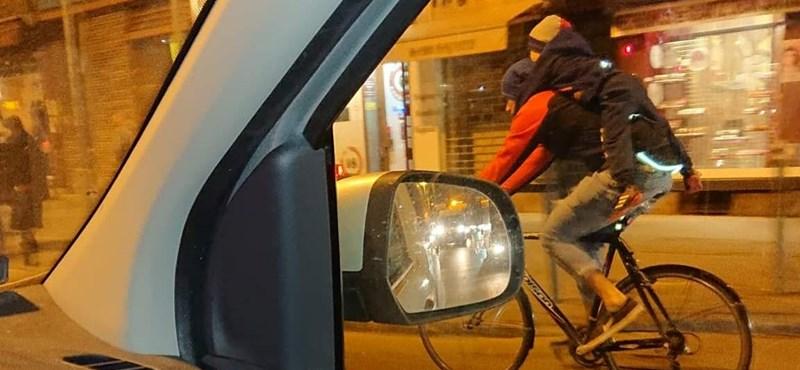 Kisgyerekkel a nyakában biciklizett egy férfi Budapesten