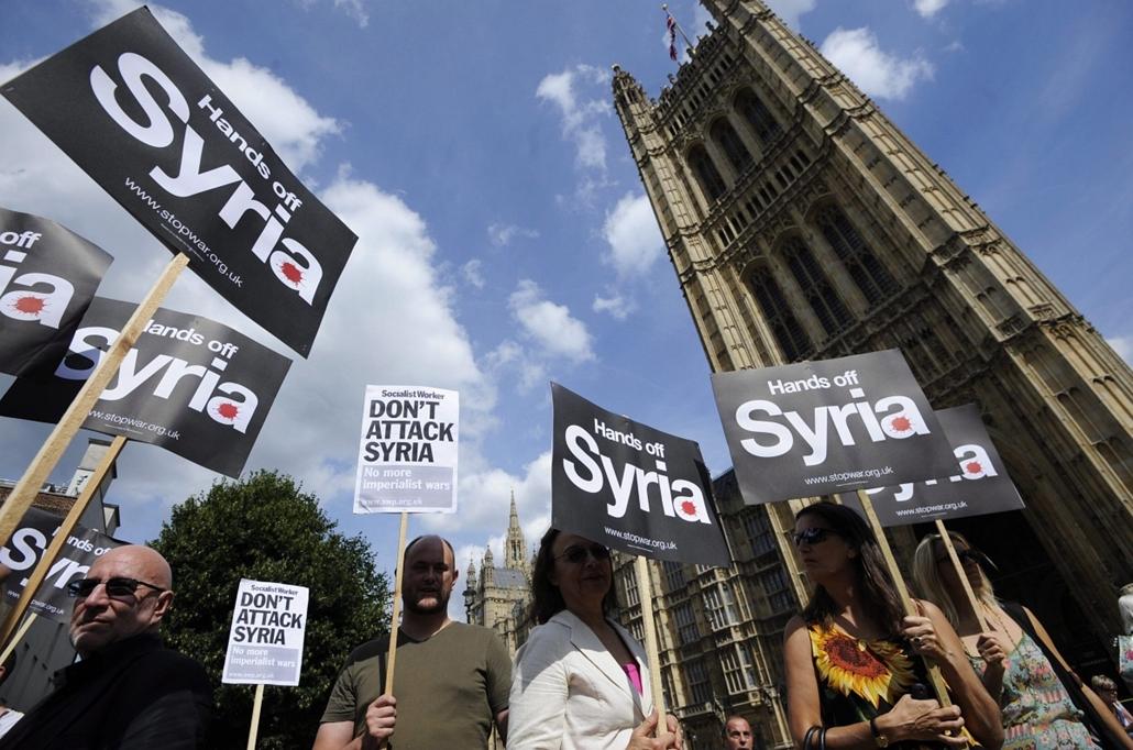 London: Tüntetők transzparensekkel tiltakoznak egy esetleges brit katonai beavatkozás ellen a londoni parlament épülete előtt, ahol a brit parlament a szíriai vegyifegyver-támadásra adandó válaszról vitázik