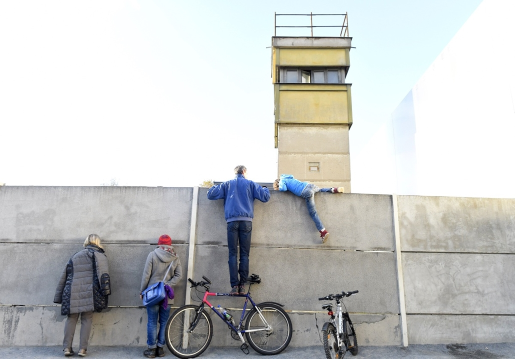 afp. Berlini fal leomlásA 25 éve 2014.11.09. People climb at the remains of the Berlin Wall at the Bernauer Street memorial site in Berlin on November 8, 2014. Germany kicked off celebrations of the 25th anniversary of the epochal fall of the Berlin Wall