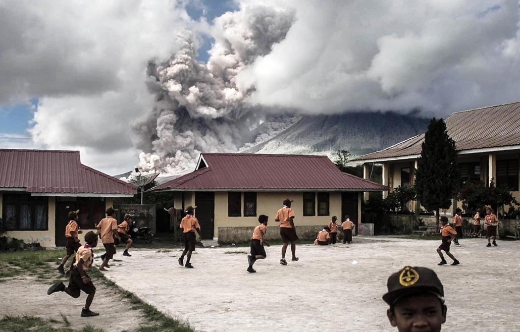 best of 2017 - Gyerekek fociznak egy álltalános iskola udvarán Karo kormányzóságban a háttérben sűrű hamufelhőt lövell ki a Sinabung tűzhányó a Szumátra szigetén