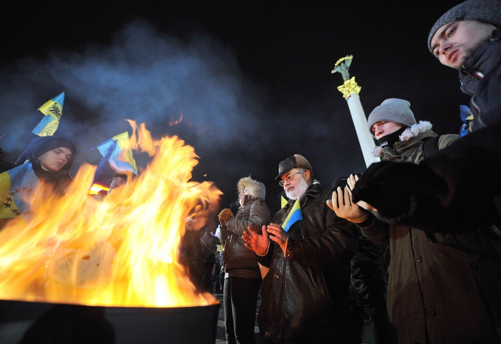 afp. nagyításhoz - ne használd - 2013.12. People warm themselves around a bonfire during a rally of the pro-European movement in central Kiev, on November 27, 2013, on the fourth day of protests over the government's decision to scrap a key pact with the