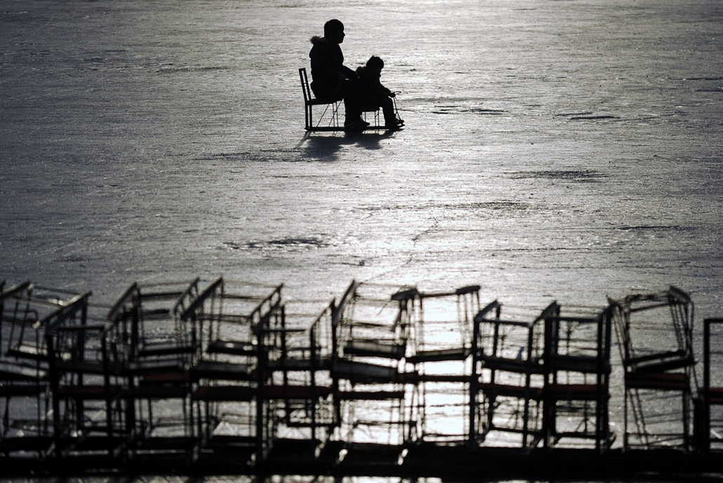 afp. hét képei - 2014.01.02. Kína, Peking - A family rides a sled on a frozen lake in Beijing on January 2, 2014. Beijing's lakes attracts scores of tourists and locals who use its frozen surface for skating and ice swimming.