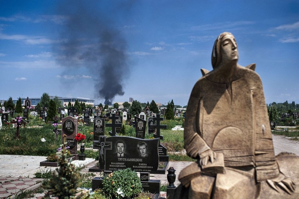 afp. Ukrajna, Donyec - 2014.05.26. Black smoke billows from Donetsk international airport, seen behind a cemetery, during heavy gun battle between the Ukrainian army and pro-Russian militants in the eastern Ukrainian city of Donetsk on May 26, 2014. Ukrai