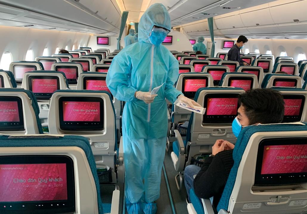 MAGYÍTÁS NE HASZNÁLD A Vietnam Airlines léágiutaskísérője védőfelszerelésben szolgál fel egy európából Vietnámra tartó járaton