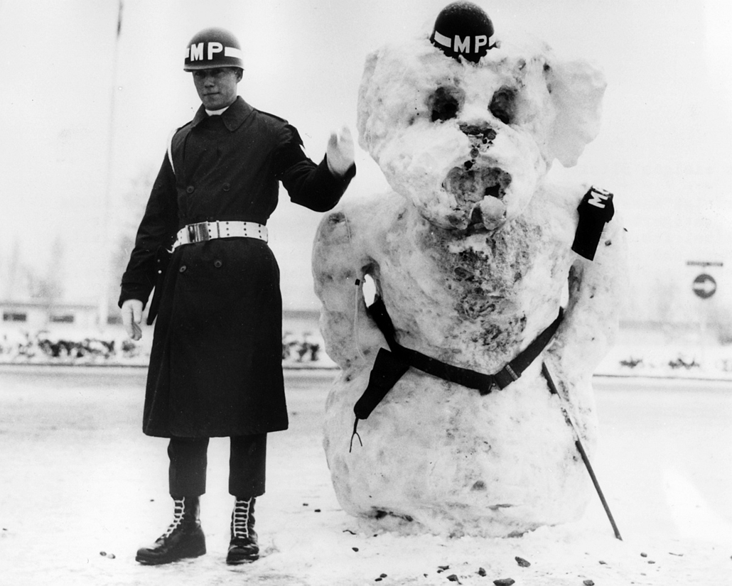 afp. hóember, 1967. amerikai katona hóemberrel - The U.S. soldier Roy J. Fiveash stands next to a snowman who helps him, dressed with badges and utensils of an American military policeman, to control the traffic in Stuttgart Vaihingen on the 14 December 1