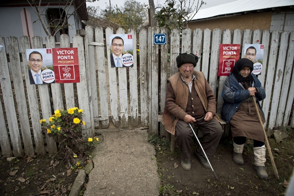 afp. hét képei - 2014.11.11. Floroaica, Románia, An elderly couple sits on a bench in front of the fence of their home covered with election campaign poster in support of Romanian Prime Minister Victor Ponta in Floroaica village on November 11, 2014. Pont