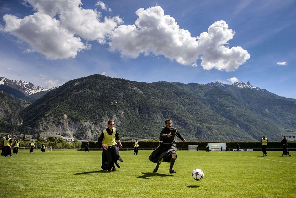 afp. az év sportfotói 2014. Riddes, Svájc, 2014.05.25. Seminarians of the International Seminary of Saint Pius X vie wearing their cassocks for the ball during a football game on May 25, 2014 in Riddes, Western Switzerland. After a whole week dedicated to