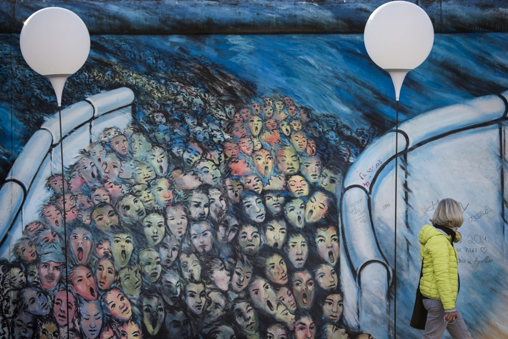 """afp. Berlini fal leomlásA 25 éve 2014.11.09. A woman passes by the """"light border"""" (Lichtgrenze) light installation along remains of the Berlin wall at East Side Gallery in Berlin on November 8, 2014. Germany kicked off celebrations of the 25th anniversary"""