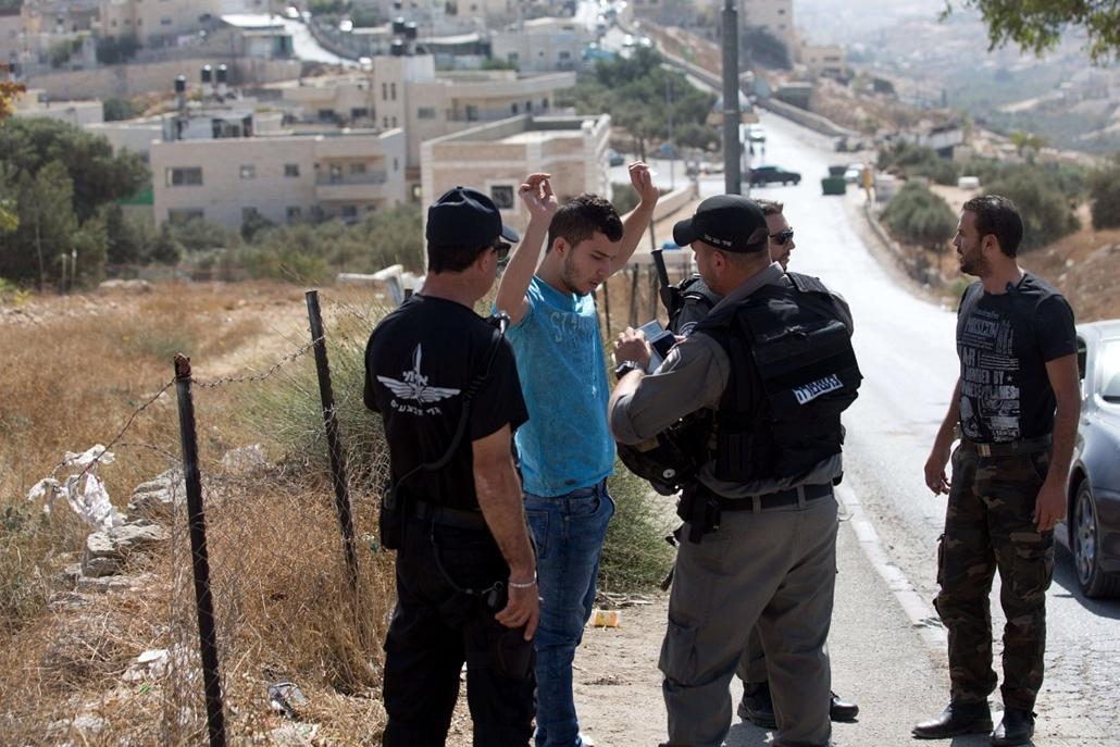 afp.izraeli-palesztin konfliktus 2015 - Jeruzsálem, rendőri ellenőrzés a határon, 2015.10.14. Israeli border policemen check a Palestinian driver on a road linking the Palestinian neighbourhood of Jabal Mukaber in East Jerusalem and Jerusalem on October 1