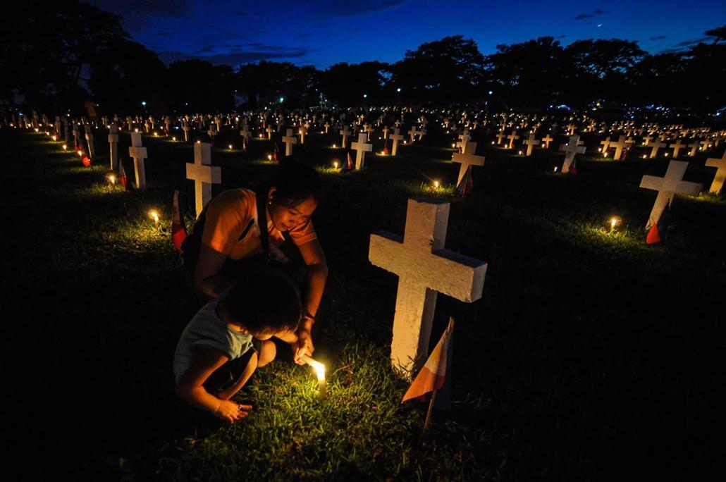 afp.16.11.01. Halottak napja mindenszentek nagyítás Fülöp-szigeteki nő és fia gyertyát gyújtanak az Nemzeti Hősök temetőjében Taguig városban , Manila, Fülöp-szigetek, 2016. november 1-jén