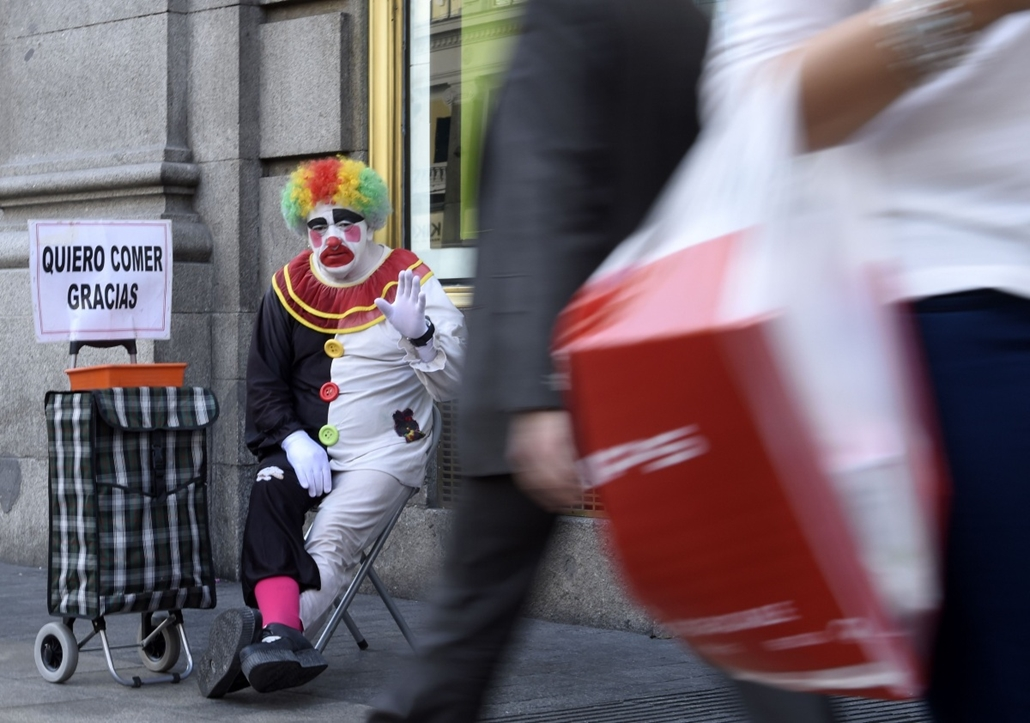 afp. hét képei - Madrid, Spanyolország, 2014.10.28. koldus bohóc - Rayito, a beggar dressed as a clown waves as he sits next to a placard reading I want to eat, thank you in Gran Via street, in the centre of Madrid, on October 28, 2014.