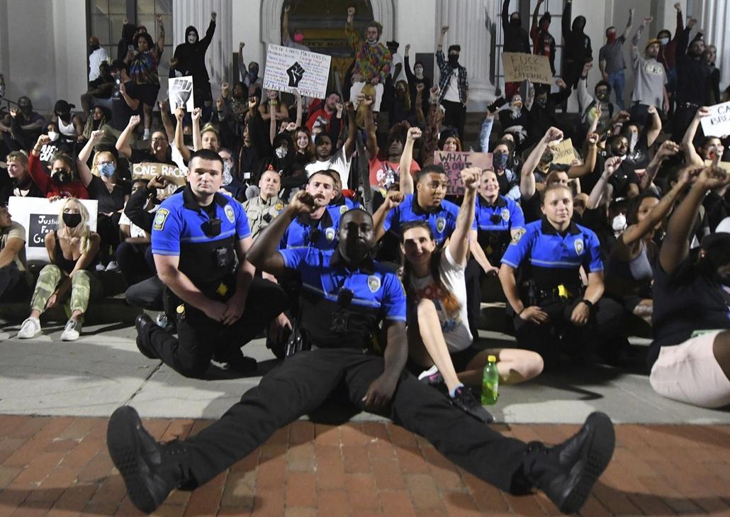!AP! nagyítás- !AP! 20.07.01ig! mti.20.06.02. Rendőrök együtt ülnek a George Floyd fekete bőrű férfi halála miatt tiltakozó tüntetőkkel a városháza előtt, az észak-karolinai Wilmingtonban 2020. június 1-jén.