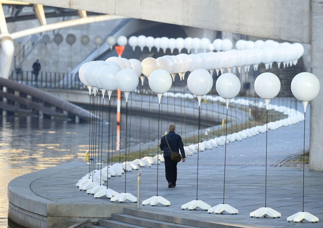 afp. Berlini fal leomlásA 25 éve 2014.11.09. A man walks past a row of lanterns that are part of the light installation Lichtgrenze (Light border) on the course of the former Berlin wall near the Reichstag building in Berlin on November 7, 2014. Around 80
