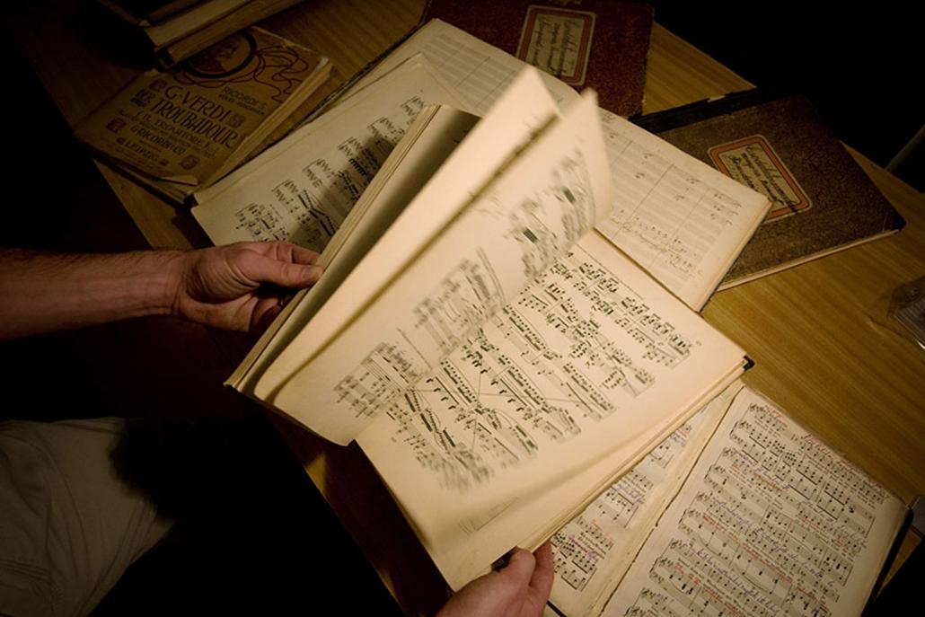 Karczag Márton, az archívum munkatársa kottákat rendez.