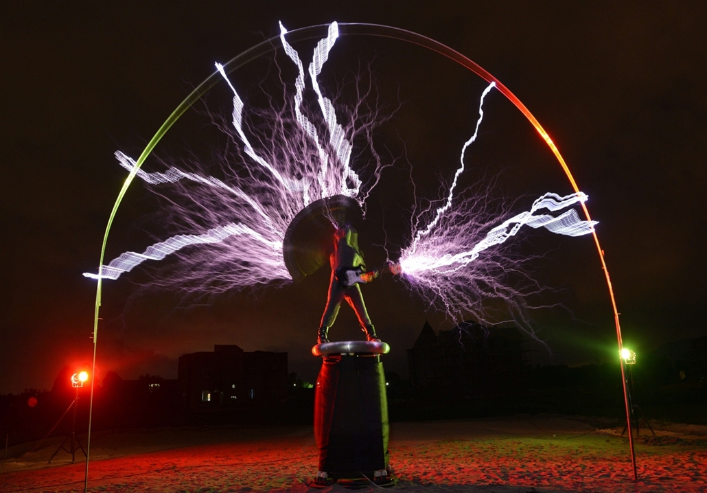 "Elektormos gitáros, The guitarist of the band ""Lightningfan"" Wang Hongbin (C) creates lightning with a Tesla Coil in their village outside of Fuzhou in China's Fujian province on June 24, 2013. The Tesla Coil invented by Nikola Tesla in 1891 is a transfor"