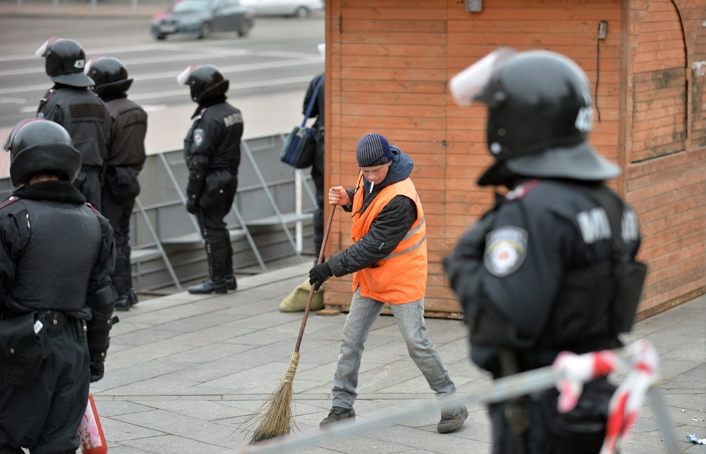 afp. nagyításhoz - ne használd - 2013.11.30. A communal worker sweeps after clashes with police on Independence Square in Kiev  on November 30, 2013.  Dozens of protesters were wounded in Ukraine's capital early Saturday when police brutally dispersed dem