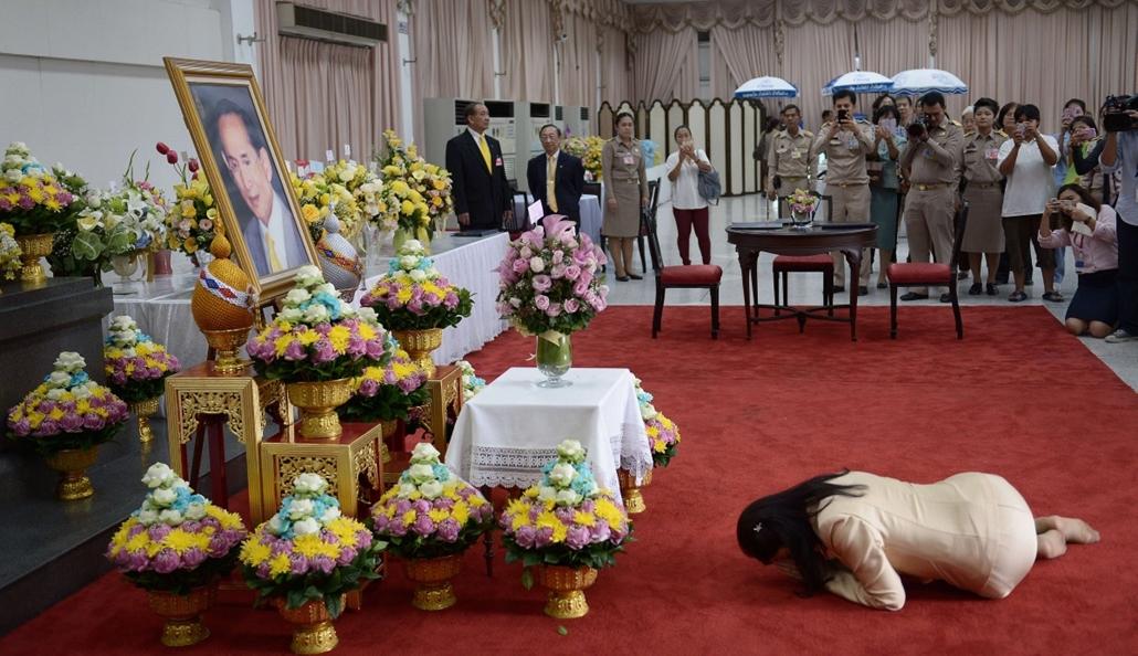 afp. a hét képei - Bangkok, Thaiföld  2014.10.06. Jinglak Sinavatra volt thaiföldi miniszterelnök (j) imádkozik IX. Ráma (Bhumibol Aduljadedzs) thaiföldi király felépüléséért az uralkodó portréja előtt a bangkoki Sziriradzs kórházban 2014. október 6-án, a
