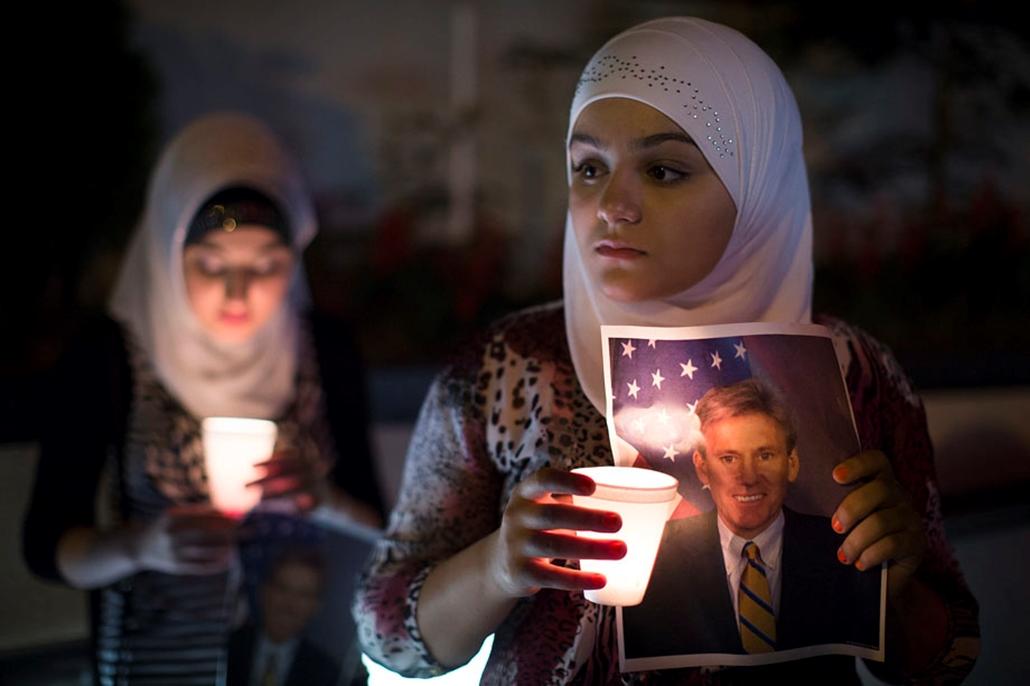 A líbiai amerikai követség előtt tartja Christopher Stevens fényképet egy kislány egy gyertyás megemlékezésen. Az amerikai nagykövetet a feldühödött tömeg ölte meg két nappal azelőtt. arab világ, tüntetések, mohammed próféta