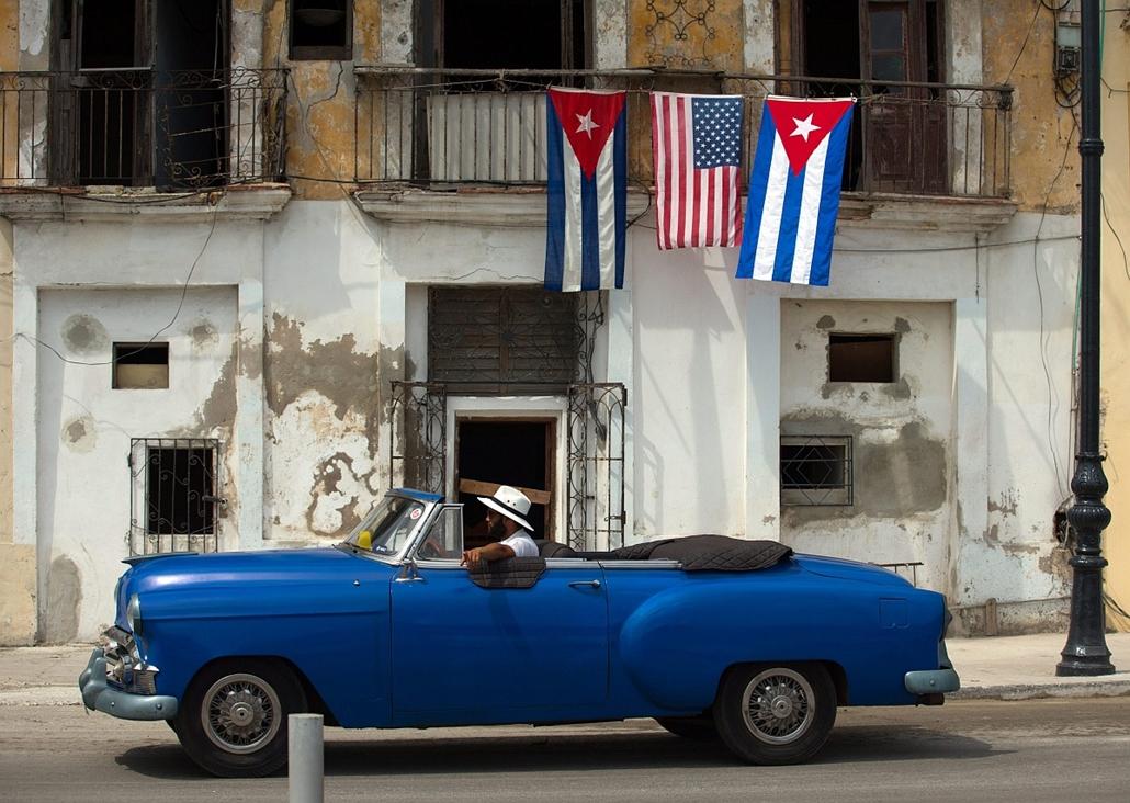 epa.16.03.20. - Havanna, Kuba: Veterán amerikai autó megy egy amerikai (k) és két kubai nemzetiszínű zászlóval díszített épület előtt Havannában. - 7képei