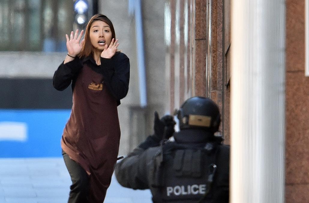 afp. Sydneyi túszdráma - 2014.12.15. Rohamrendőrök annak a sydneyi kávéháznak a közelében 2014. december 15-én, ahol iszlamisták túszul ejtettek több embert. A rendőrség legalább egy fegyveres túszejtőről beszélt, azt viszont továbbra sem közölte, hogy há