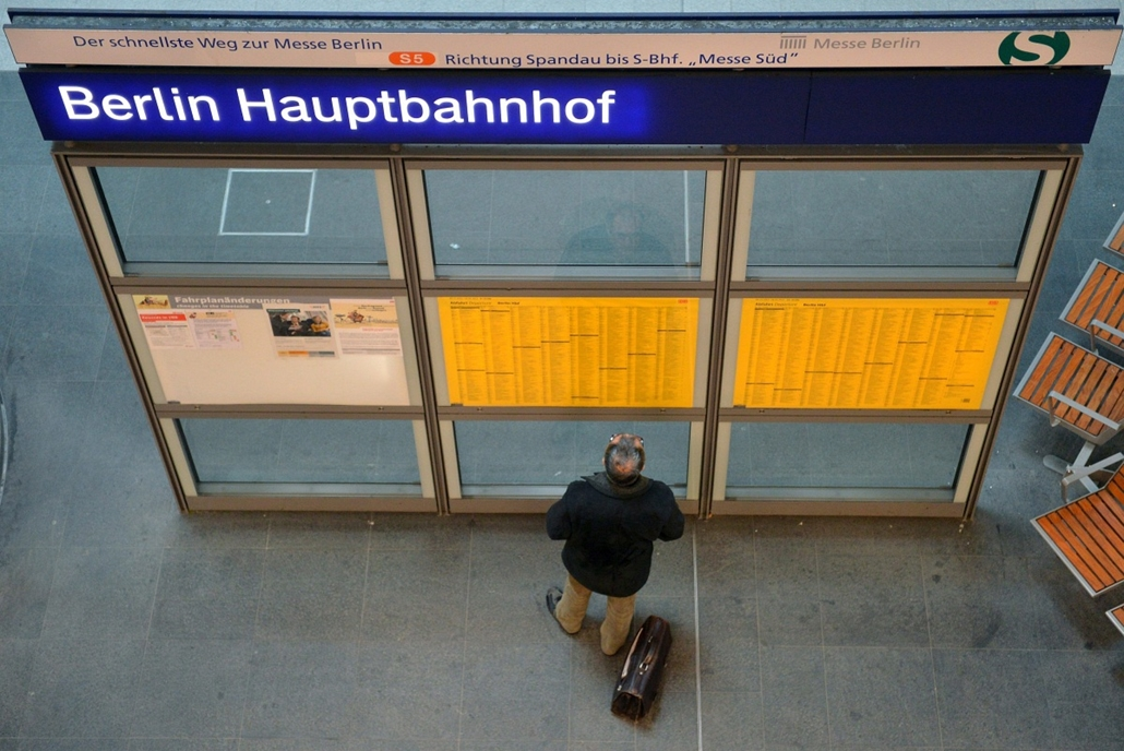 Berlin, bomba, pályaudvar - A menetrendet tanulmányozza egy utas a berlini Főpályaudvaron 2013. április 3-án, miután fel nem robbant II. világháborús szovjet bombát találtak a közelben. A pályaudvarról északra vezető vonalon vágányzárt rendeltek el, és a