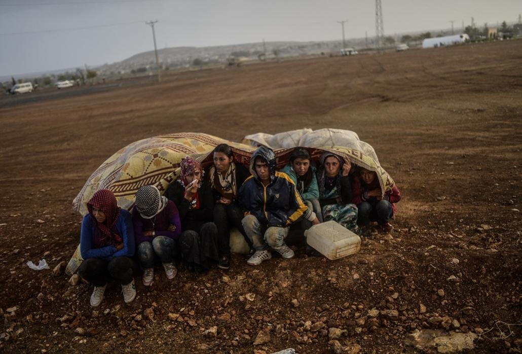 afp. hét képei - Suruc, Törökország, 2014.10.02. Szíriai kurdok, menekültek, Syrian Kurds take cover from the rain in the southeastern town of Suruc in the Sanliurfa province after crossing the border between Syria and Turkey after mortars hit both sides
