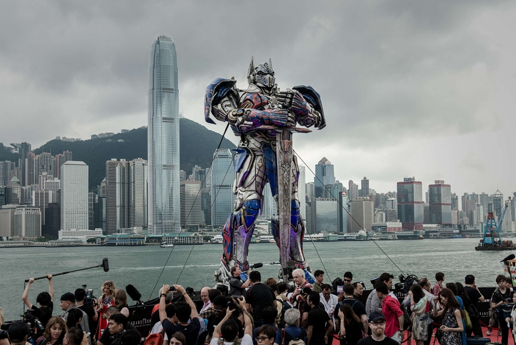 afp. a hét képei 0616-0621 - Knía, Hongkong 2014.06.19. A 20 foot-tall Optimus Prime figure is surrounded by journalists before the world premiere of Hollywood movie Transformers 4 in Hong Kong on June 19, 2014.  Hollywood director Michael Bay's latest fi