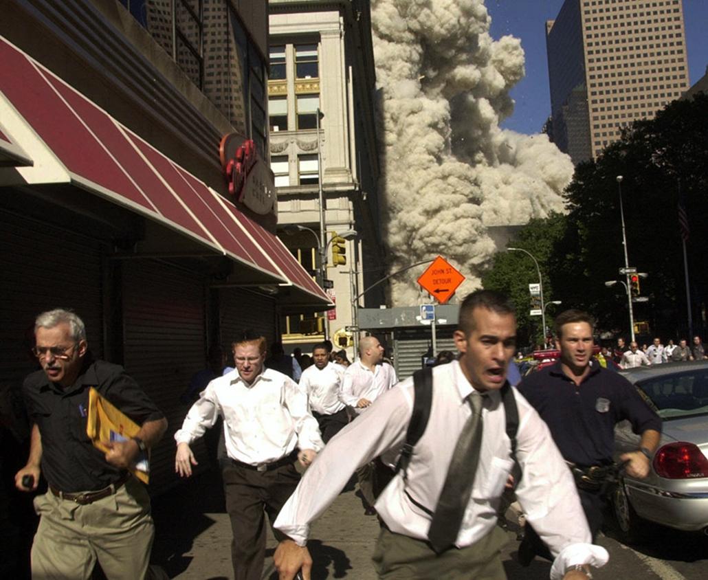 Emberek menekülnek New Yorkban a Világkereskedelmi Központ lehulló épületeinek törmeléke elől 2001. szeptember 11-én.