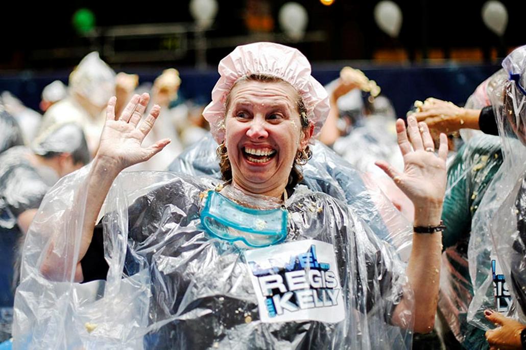 Esőköpenybe öltözött nő nevet az ABC televíziós társaság épülete előtt az utcán New Yorkban, amikor a világ legnagyobb tortacsatájával Guinness-világcsúcsot állítanak fel tortadobálók  egy tévéműsorban.