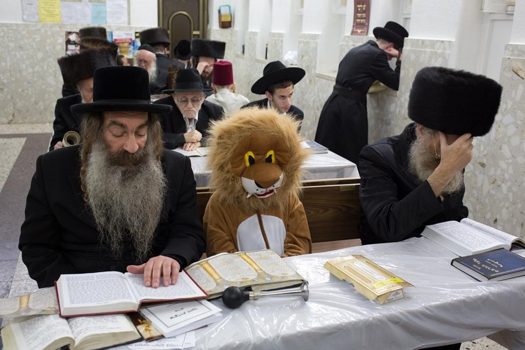 afp.15.03.04. - Bnei Brak, Izrael: Ultraortodox zsidók és egy gyermek Eszter könyvének olvasása közben a Purim alatt. - 7képei