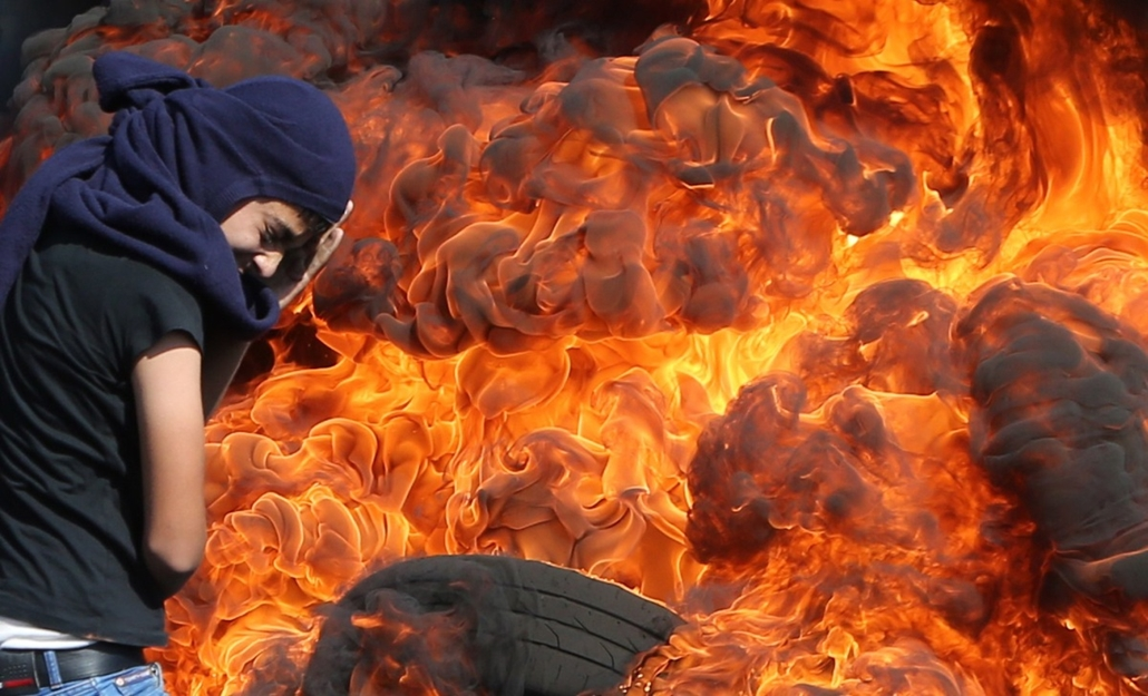 afp. hét képei - Kfar Qaddum, 2014.10.26. palesztin tüntető, A Palestinian protester protects his face as he stands in front of burning tires during a demonstration against the expropriation of Palestinian land by Israel in the village of Kafr Qaddum, nea