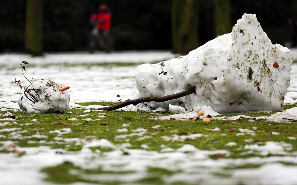 afp. hóember, 2013.01.28. olvadó hóeber, Düsseldorf park, A melting snowman lays in a park in Duesseldorf, western Germany, on January 28, 2013. After days of a cold spell, temperatures rise again over the freezing point in many parts of the country.
