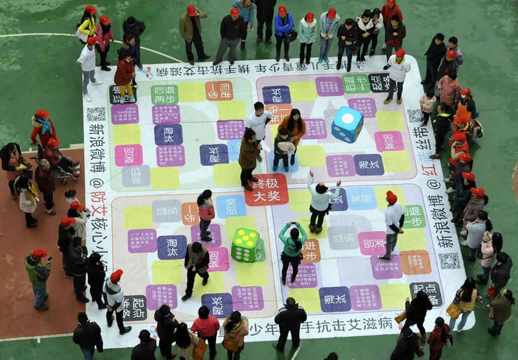 afp.14.11.29. - Hefei, Kína: Fiatalok az AIDS megelőzésének ismeretit oktató társasjáték körül a kínai Hefeiben 2014 novemberében. - aids világnap nagyítás