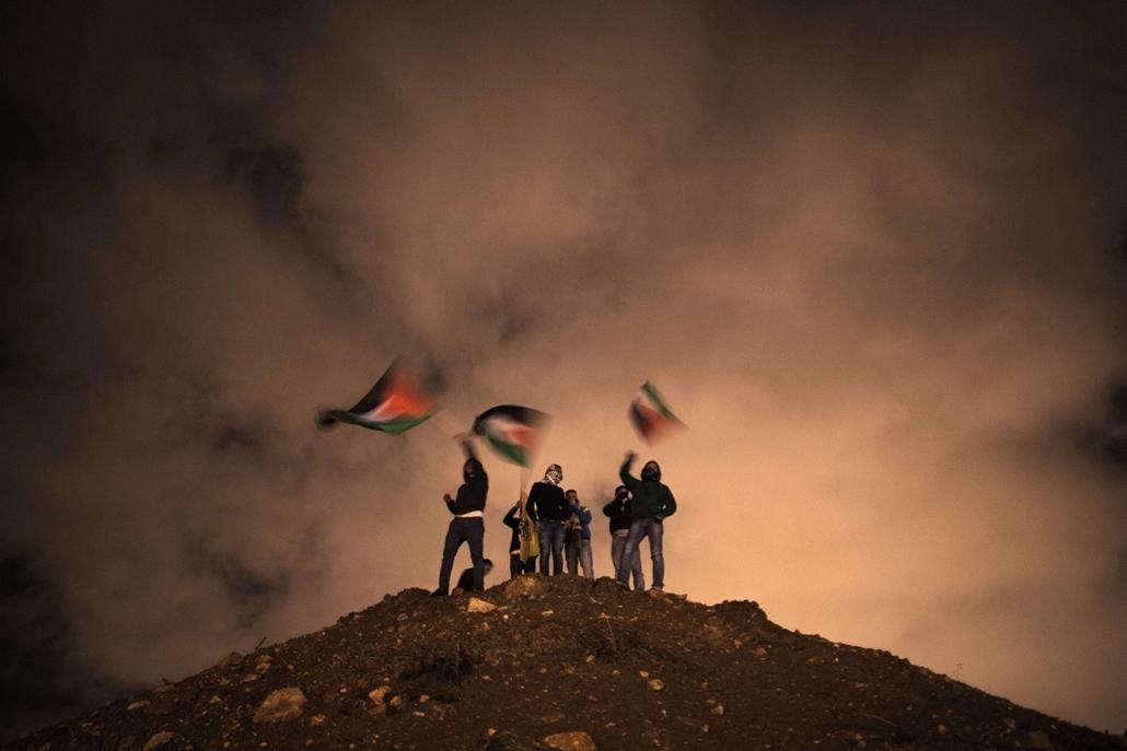 afp. hét képei - Jeruzsálem 2013.12.31. palesztin, zászló - Palestinians wave their national flag as they await the release of Palestinian prisoners to Jerusalem December 31, 2013.  Israel has freed 26 Palestinian prisoners under peace talks brokered by U