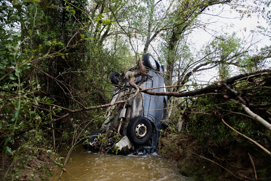 afp. hét képe - Saint-Pargoire, Franciaország, árvíz, 2014.09.30. A picture taken on September 30, 2014 shows a crashed car after floodwater streamed down a road in Saint-Pargoire, near Montpellier, southern France.  France declared a state of natural dis