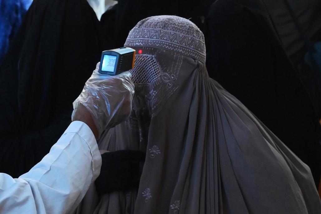 MAGYÍTÁS NE HASZNÁLD  Egy egészségügyi tisztviselő ellenőrzi egy utas testhőmérsékletét Pakisztánban a Lahore vonatállomáson