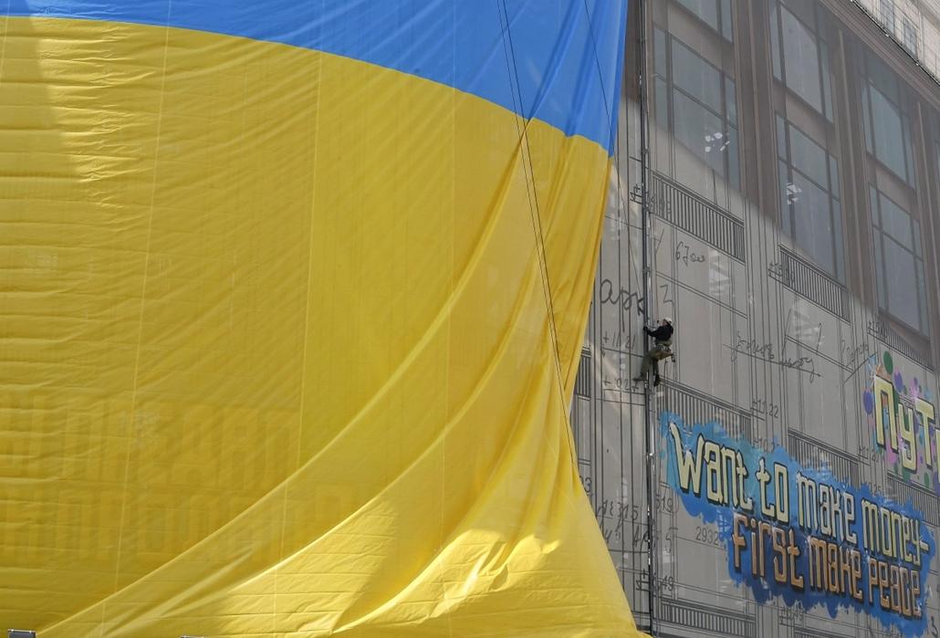epa. hét képei - Kijev, 2014.05.06. Hatalmas ukrán zászlót feszítenek ki alpinisták egy kijevi áruházra 2014. május 6-án.